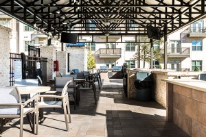Resident patio with grills and table seating under pavilion.